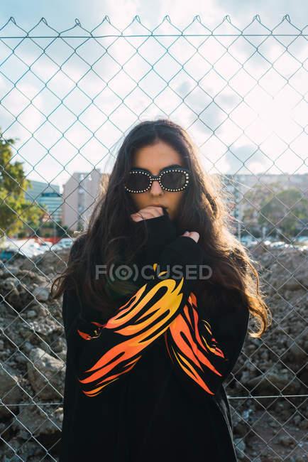 Portrait of brunette girl in sunglasses wearing sweatshot with flames print — Stock Photo