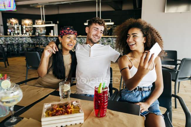 Чоловік і два Веселі дівчата беручи selfie в кафе таблиці — стокове фото