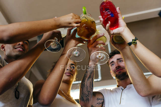 Low angle view of friends clinking cocktails in bar — Stock Photo