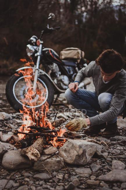 Homme gardant le feu brûlant sur fond de moto garée sur l'estran rocheux — Photo de stock