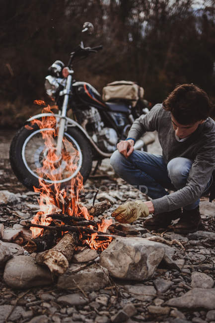 Man keeping campfire burning on background of parked motorcycle on rocky shore. — Stock Photo