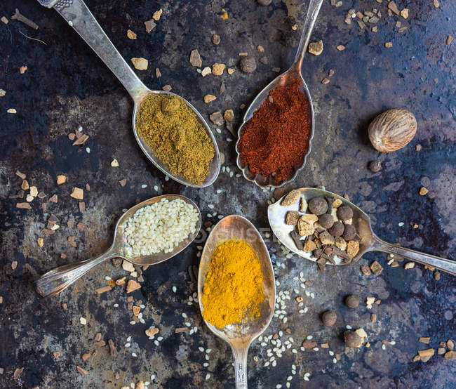 From above view of five spoons with seasonings composed in circle on metal surface. — Stock Photo