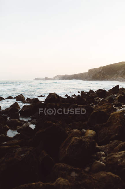 Scenic landscape of rocky beach at foggy bay — Stock Photo
