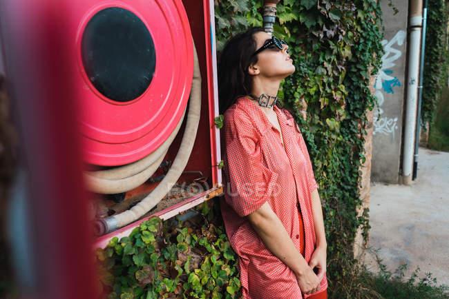 Brunette woman in sunglasses posing beside fire hose — Stock Photo