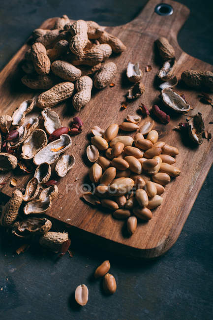 Close up view of pile of peanuts and peels on wooden cutting board on dark surface — Stock Photo