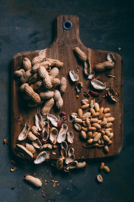 Top view of peeled and shelled peanuts on wooden board with peels — Stock Photo