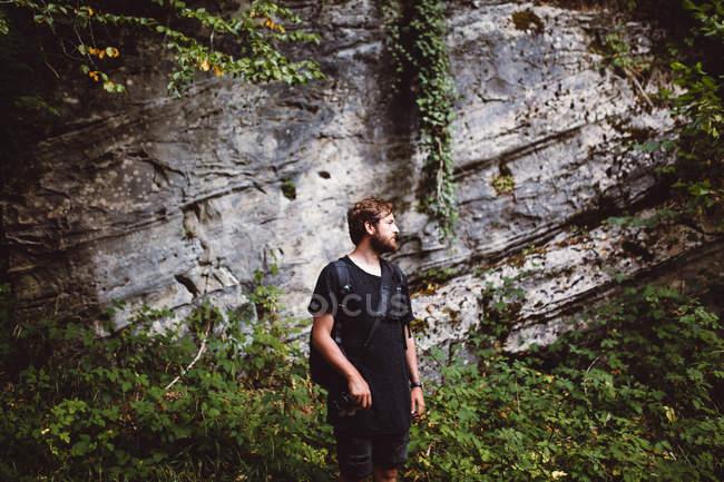 Homem posando penhasco coberto com plantas na natureza — Fotografia de Stock