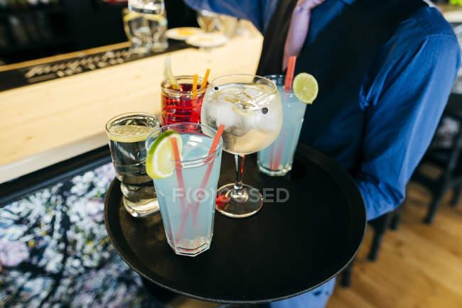Ernte-Kellner mit Tablett mit verschiedenen Cocktails an der Theke — Stockfoto