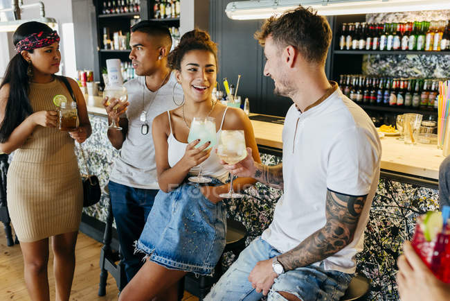 Cheerful friends drinking cocktails by bar counter — Stock Photo