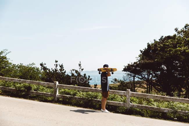 Вид сбоку на человека, держащего скейтборд на плече и любующегося мысом — стоковое фото