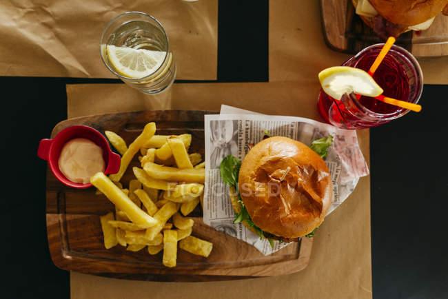 Сверху Аппетитный гамбургер с картофелем фри, подается на стол в кафе — стоковое фото