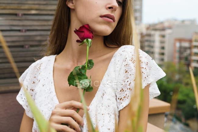 Mulher sensual colheita posando com rosa vermelha na varanda — Fotografia de Stock