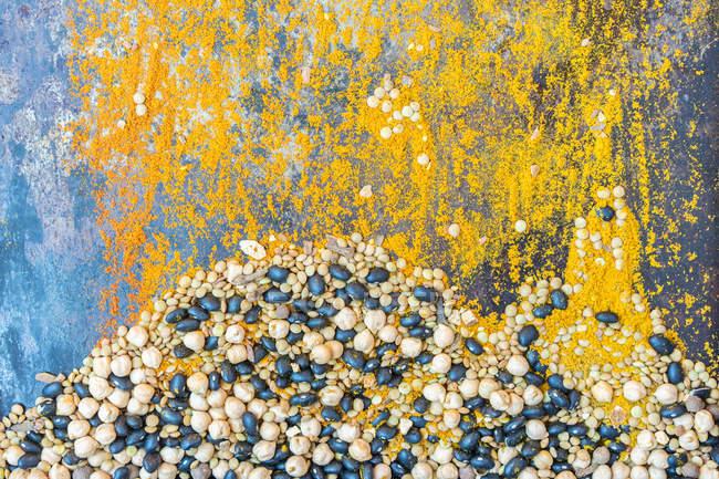 Vista superior de especiarias aterradas coloridas e feijões secos e ervilhas misturado na superfície de metal. — Fotografia de Stock