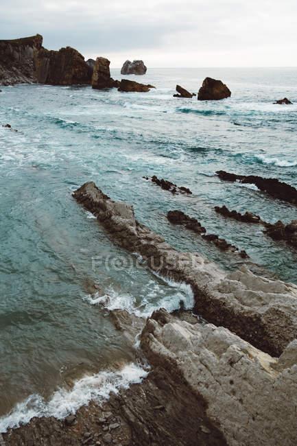 Paysage de plage rocheuse et de vagues de surf — Photo de stock