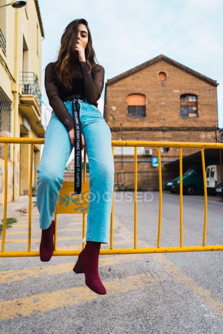 Bruna ragazza seduta alla recinzione e guardando la fotocamera — Foto stock