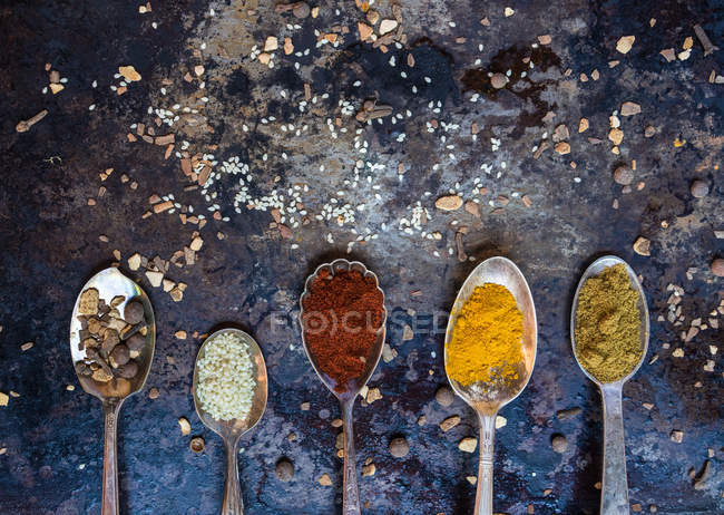 Close-up shot of silver spoons filled with various condiments in composition. — Stock Photo