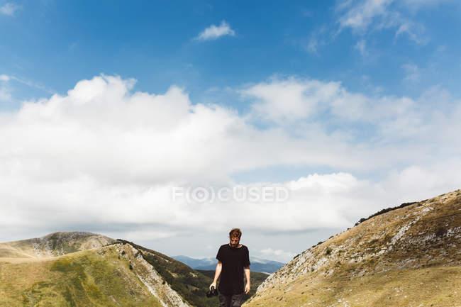 Uomo turistico a piedi alle pittoresche montagne illuminate dal sole e guardando in basso — Foto stock