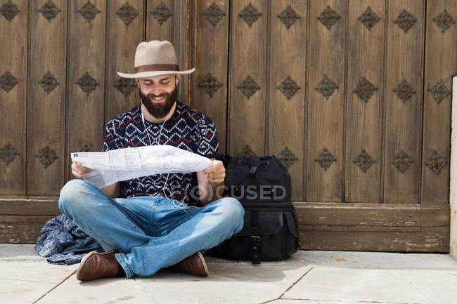 Hombre barbudo con sombrero sentado por las puertas y la lectura de mapa - foto de stock