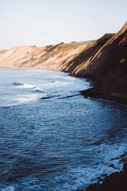 Coastal landscape with plumb shoreline and white surfing waves — Stock Photo