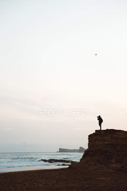 side view of silhouette of man standing on coastal cliff