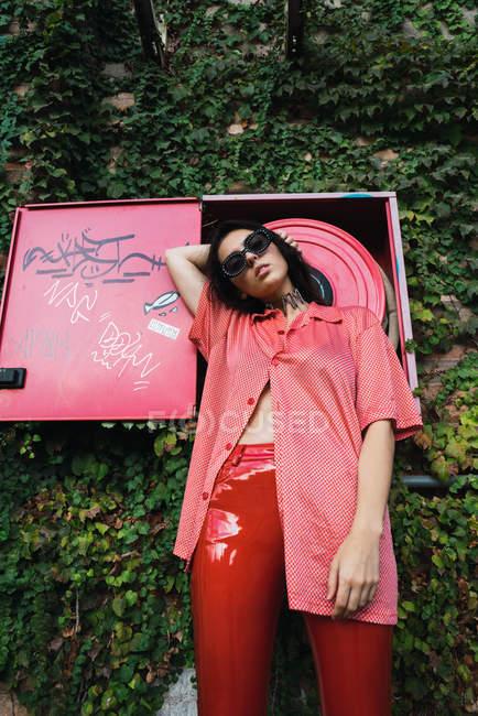 Vista de ángulo alto de la chica morena en gafas de sol con ropa roja provocativa posando sobre manguera de fuego en la hiedra abrazó fachada - foto de stock