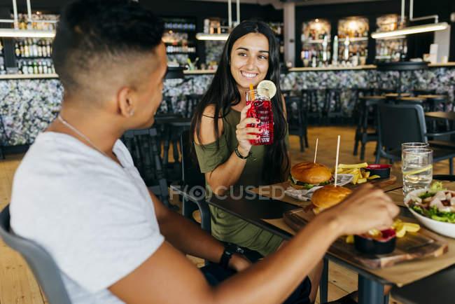 Mulher sorridente com bebida olhando para o homem no café — Fotografia de Stock