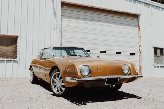 Bella auto retrò lucido parcheggiata sullo sfondo del garage bianco — Foto stock