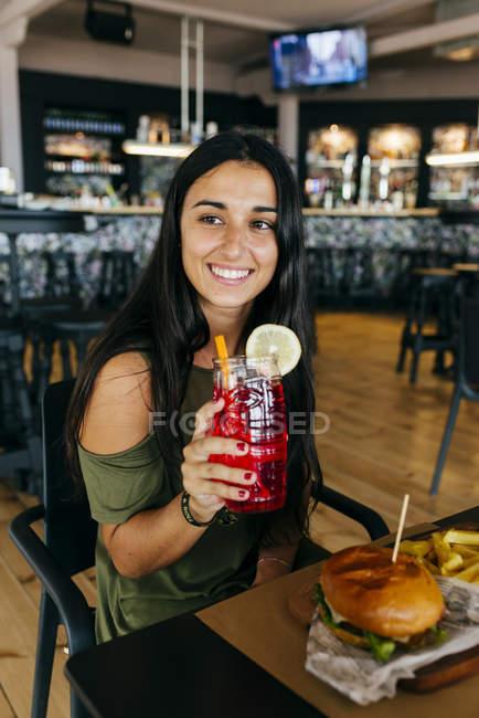 Donna con il cocktail mangia hamburger al caffè e che osserva via — Foto stock