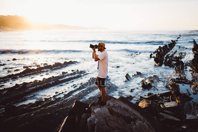 Side view of man taking shots  with camera on stone at ocean shore. — Stock Photo