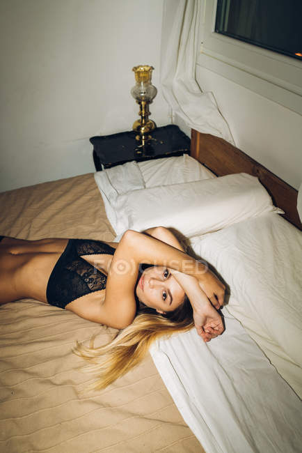 Sensual girl in black lingerie lying on bed with arms on face and looking at camera — Stock Photo