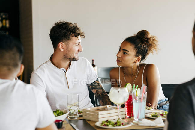 Friends sitting at cafe and looking at each other — Stock Photo
