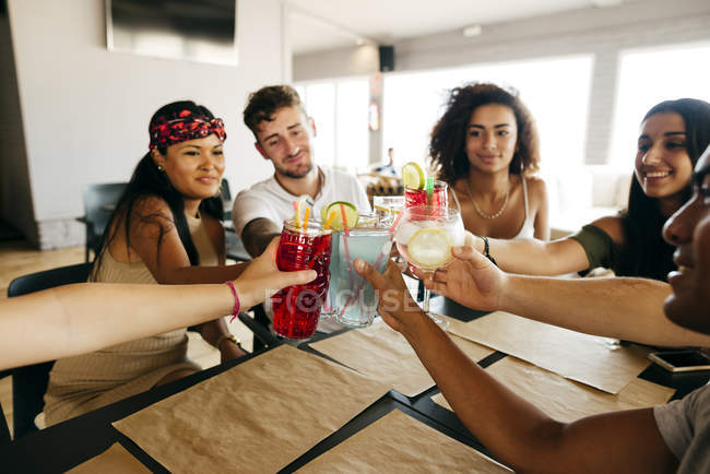 Happy friends toasting cocktails at cafe table — Stock Photo