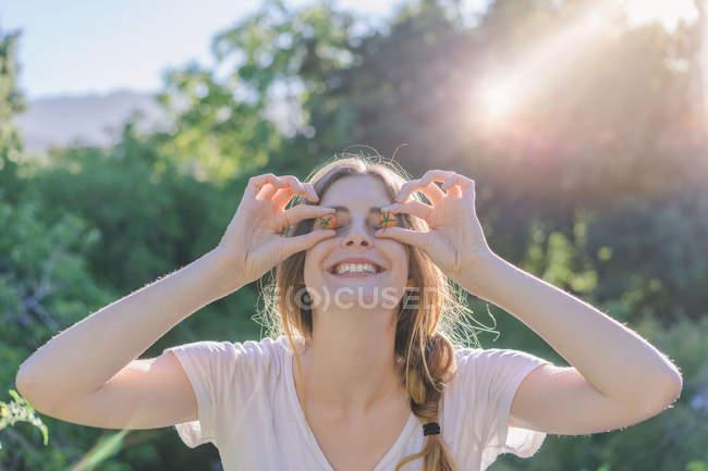 Retrato de mulher alegre cobrindo olhos com tomates cereja maduros e sorrindo — Fotografia de Stock