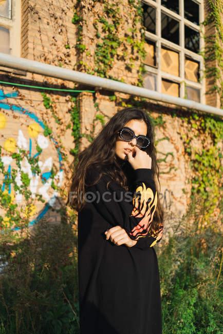Вид сбоку брюнетка девочки носить очки, глядя через плечо на камеру на уличная сцена — стоковое фото