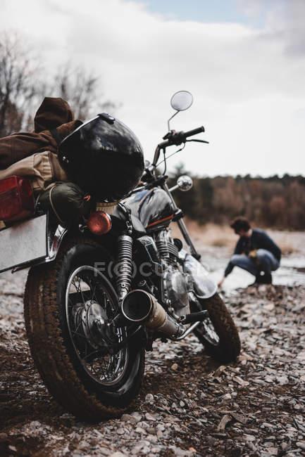 Mann, sitzend in der Nähe von Motorrad mit Reisegepäck — Stockfoto