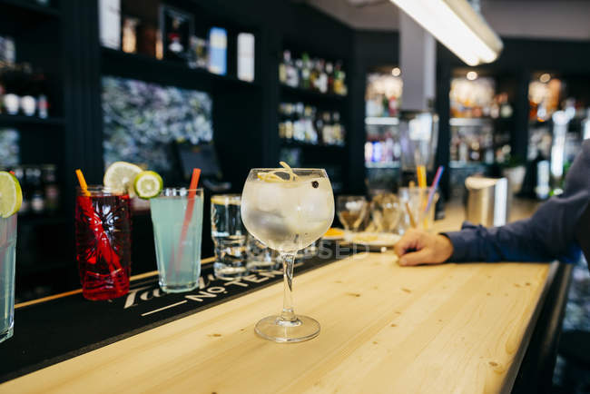 Cocktail on bar counter and hand of unrecognizable man. — Stock Photo