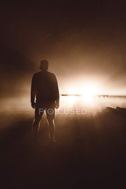 Rear view of male silhouette posing against light at brown mist. — Stock Photo