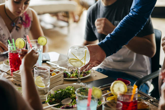 Crop waiter putting cocktail on table with people dining. — Stock Photo