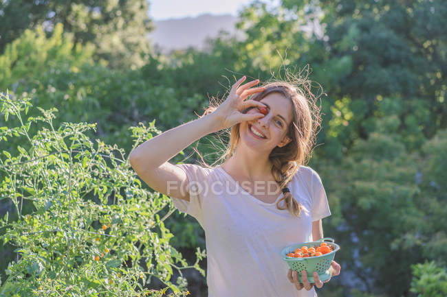 Portrait of cheerful woman covering one eye with ripe cherry tomato and smiling — Stock Photo