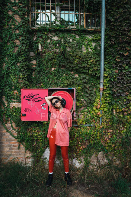 Brunette girl in sunglasses posing at fire hose box on ivy embraced building facade — Stock Photo