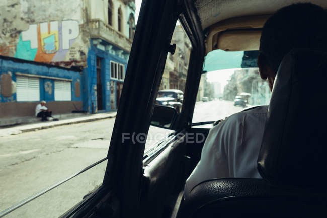 Back view of man driving car down street in poor city. — Stock Photo