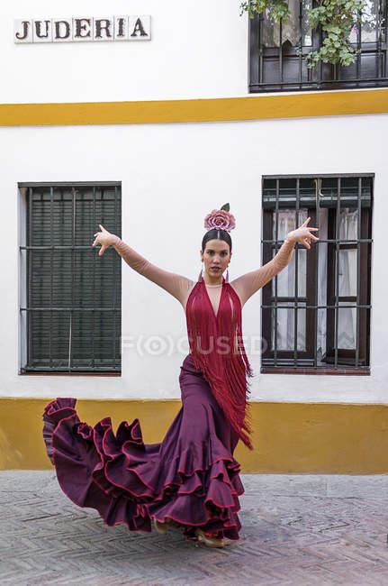 Vista frontal de la bailarina flamenca con el traje típico posando sobre la fachada del edificio rural - foto de stock