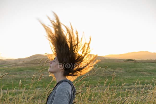 Вид збоку дівчина завивки волосся на фоні влітку поля. — стокове фото