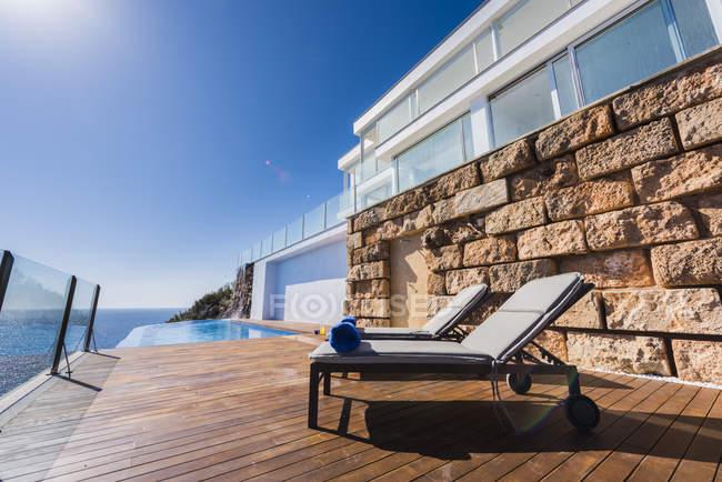 Terrazza di casa costosa residenziale con lettini e piscina — Foto stock