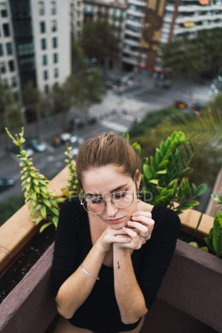 High angle view of brunette girl in eyeglasses posing with hands near chin at terrace — Stock Photo