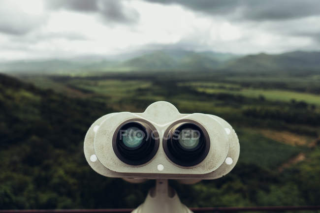Panoramic view of green valley and sight-seen binoculars under cloudy sky. — Stock Photo