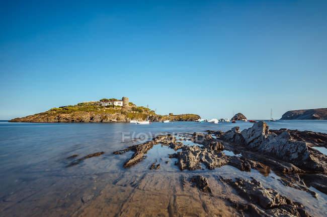 Paisagem costeira da colina iluminada pelo sol com rural abriga, no mar, Baía — Fotografia de Stock