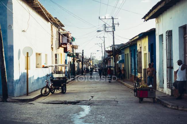 Cuba - 27 août 2016: Vue en Perspective à la rue avec la route asphaltée et les populations locales sur le trottoir. — Photo de stock