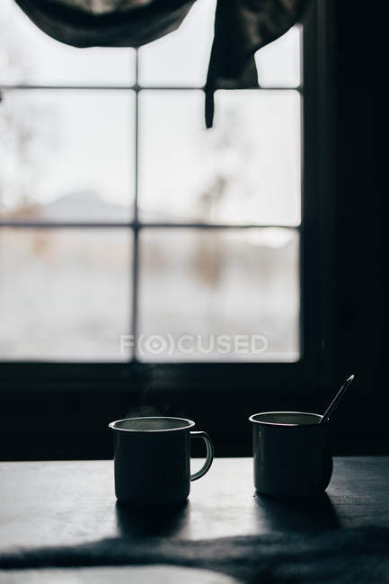 Close up view of two metallic cups on table in rural house. — Stock Photo