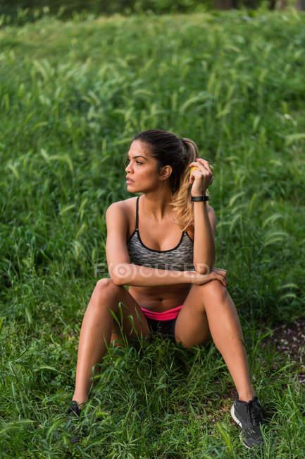 Спортсмен сидит на траве в парке и позирует — стоковое фото